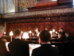 The choir rehearse in the choir stalls at Chichester Cathedral